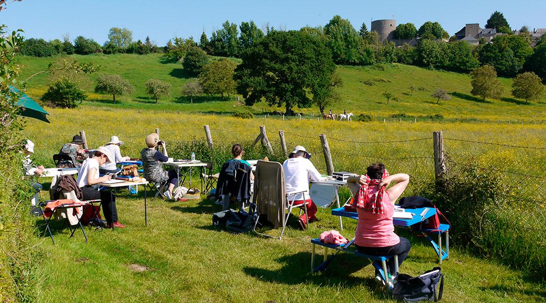 groupe de stagiaires assis dans un champ en train de peintre le paysage face a eux